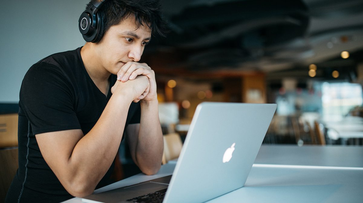 Man At Computer Watching Webinar or Live Stream Video